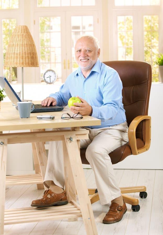 Homem mais idoso que trabalha em seu estudo foto de stock royalty free