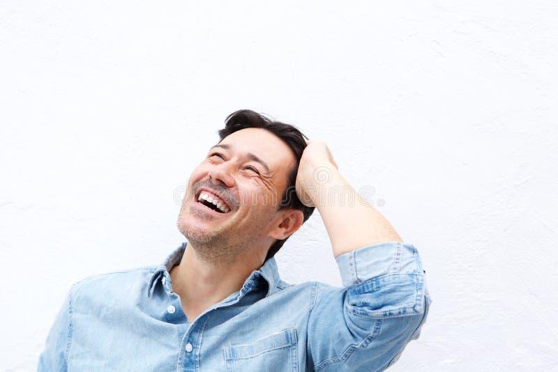 Homem mais idoso relaxado que ri com mão na cabeça contra o fundo branco foto de stock