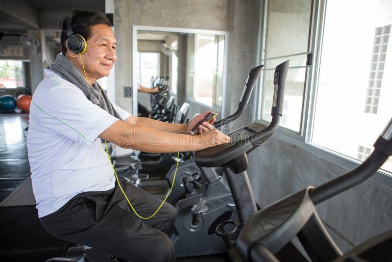 Homem mais idoso superior que exercita na música de escuta de ciclagem da máquina com os fones de ouvido e o telefone que relaxam fotografia de stock royalty free