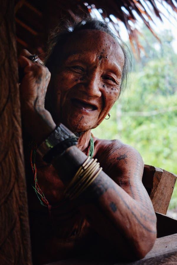 Homem mais idoso tribal que aprecia o resto da tarde em sua casa na selva imagens de stock
