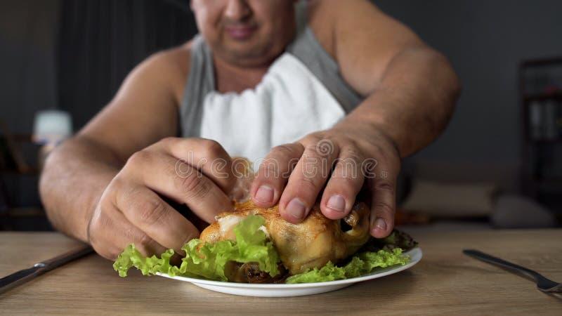 Homem mal educado que rasga o frango frito gorduroso com dedos, apego do alimento gordo fotos de stock royalty free
