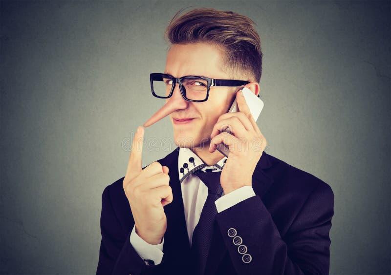 Homem manhoso novo com nariz longo que fala no telefone celular Conceito do mentiroso imagem de stock