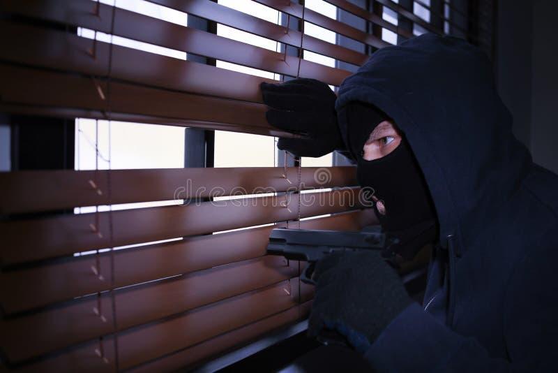 Homem mascarado com a arma que espia atrav?s das cortinas de janela Ofensa criminosa fotografia de stock royalty free
