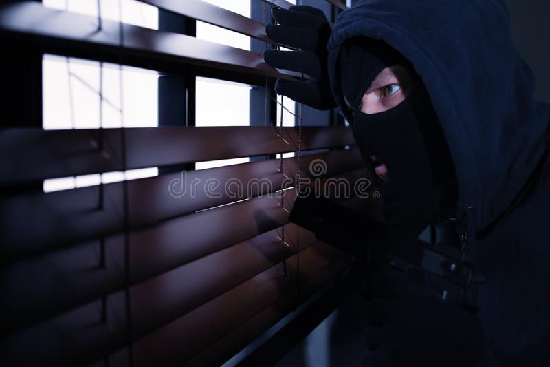 Homem mascarado com a arma que espia atrav?s das cortinas de janela Ofensa criminosa foto de stock royalty free