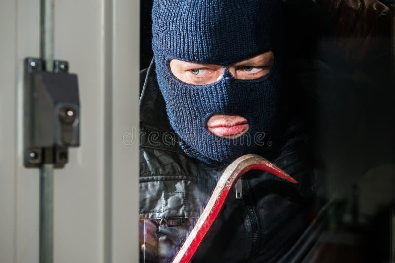 Homem mascarado sério que guarda a pé de cabra ao olhar no vento da casa foto de stock royalty free