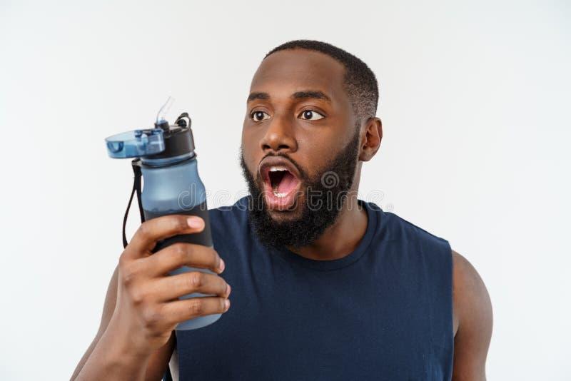 Homem masculino afro-americano do esporte do atleta com esportes de corrida com telefone celular e água potável da garrafa imagem de stock royalty free