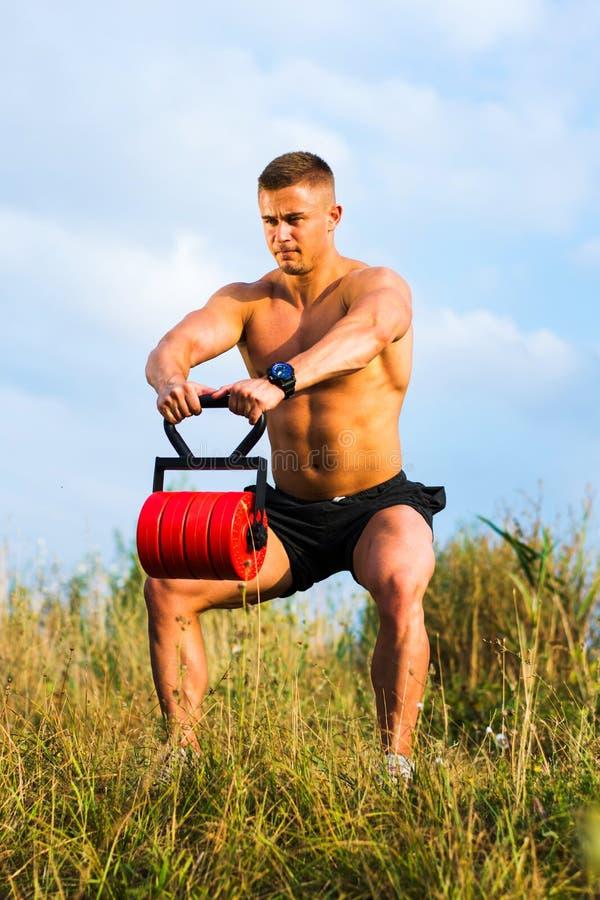Homem masculino que exercita fora com um peso imagem de stock