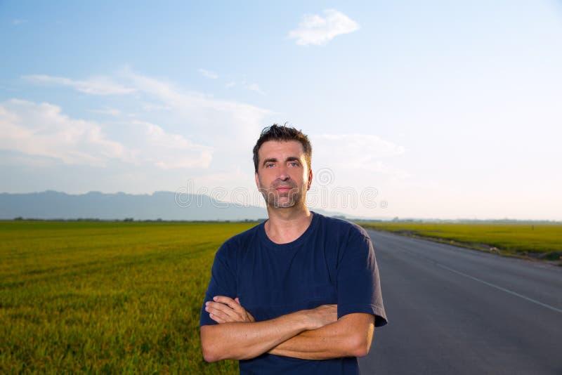 Homem meados de da idade na estrada nos prados que levantam os braços cruzados fotografia de stock royalty free