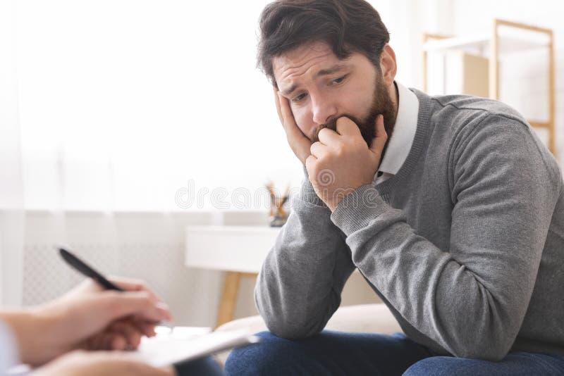Homem milenar com depressão durante a sessão da psicoterapia fotografia de stock