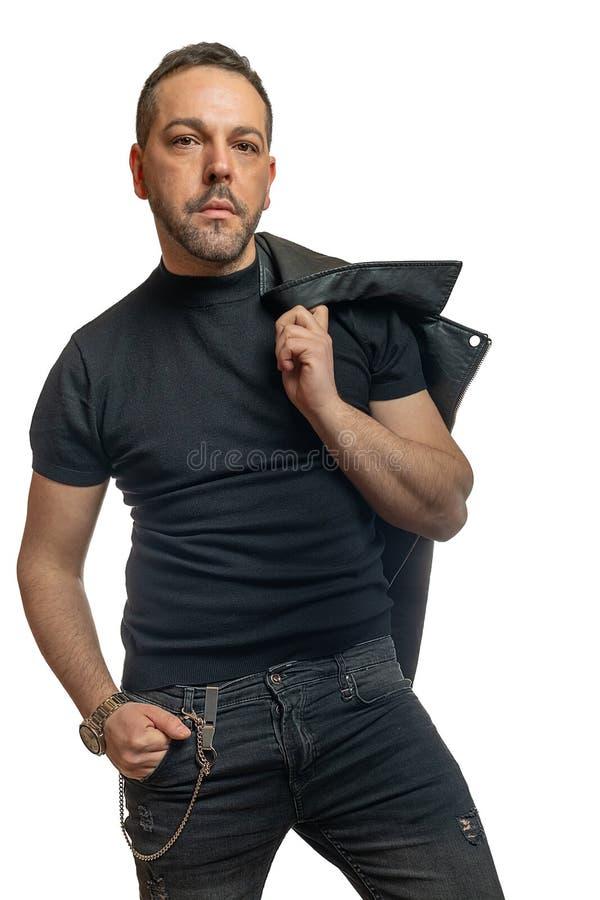 Homem modelo atrativo com a barba contra os olhares brancos do fundo na câmera foto de stock