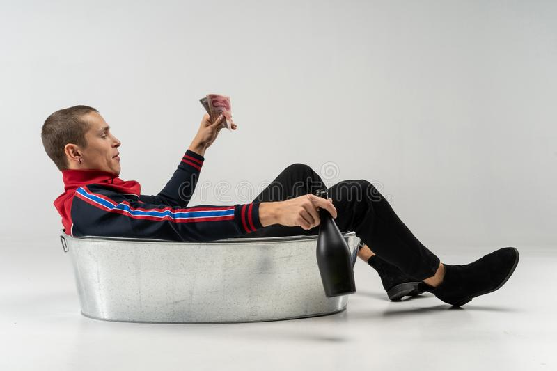 Homem modelo considerável com corte de cabelo curto no vestuário desportivo que senta-se no banho do metal no estúdio foto de stock royalty free