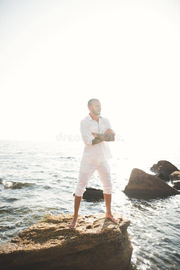 Homem modelo considerável que levanta na pedra pelo mar foto de stock