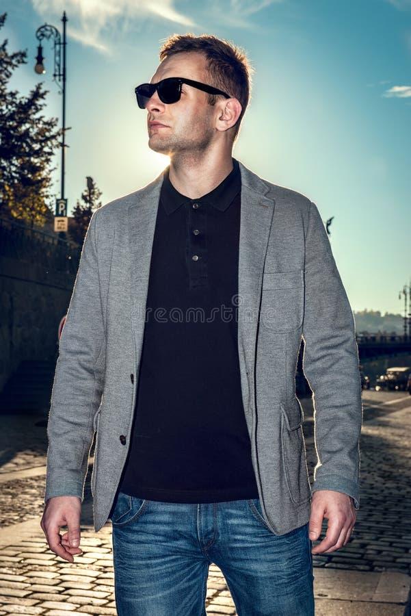 Homem modelo considerável 'sexy' à moda no estilo de vida ocasional de pano na rua nos vidros fotos de stock
