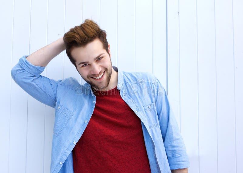 Homem moderno novo considerável que sorri com mão no cabelo fotografia de stock