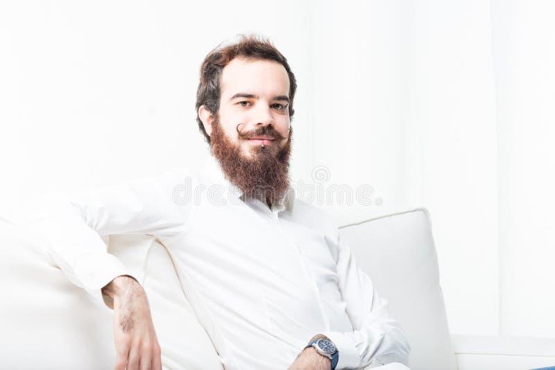 Homem moderno novo em seu sofá foto de stock royalty free