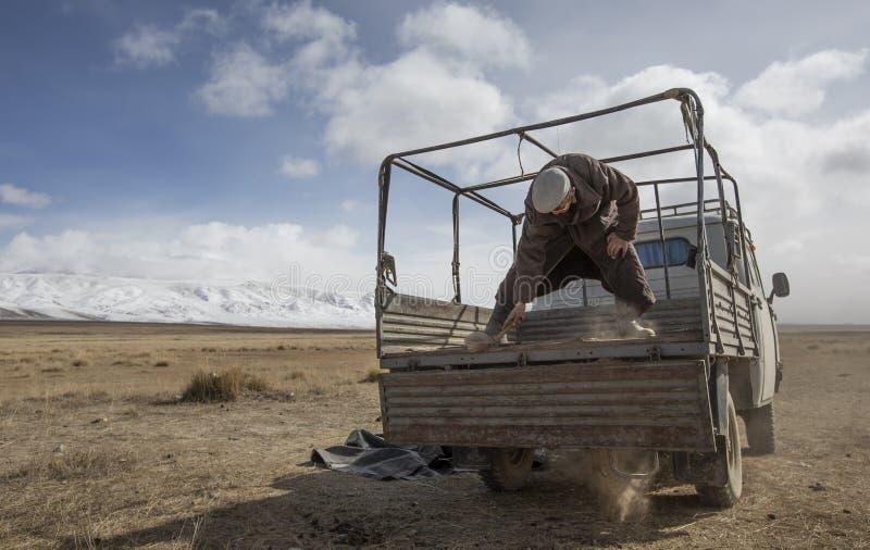 Homem Mongolian do nômadas que limpa a parte traseira de seu carro foto de stock royalty free