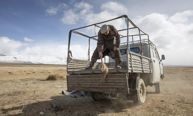 Homem Mongolian do nômadas que limpa a parte traseira de seu carro imagem de stock royalty free