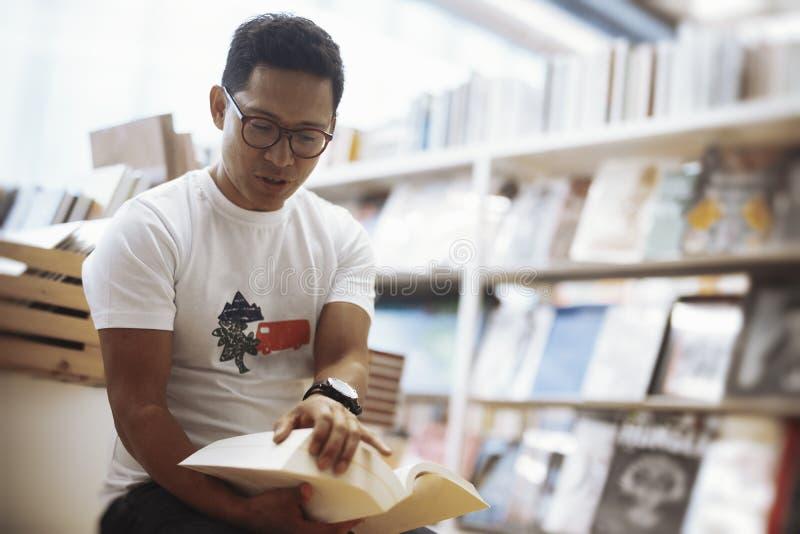 Homem moreno de óculos novo que senta-se ao lado das bibliotecas e que abre um livro imagens de stock royalty free