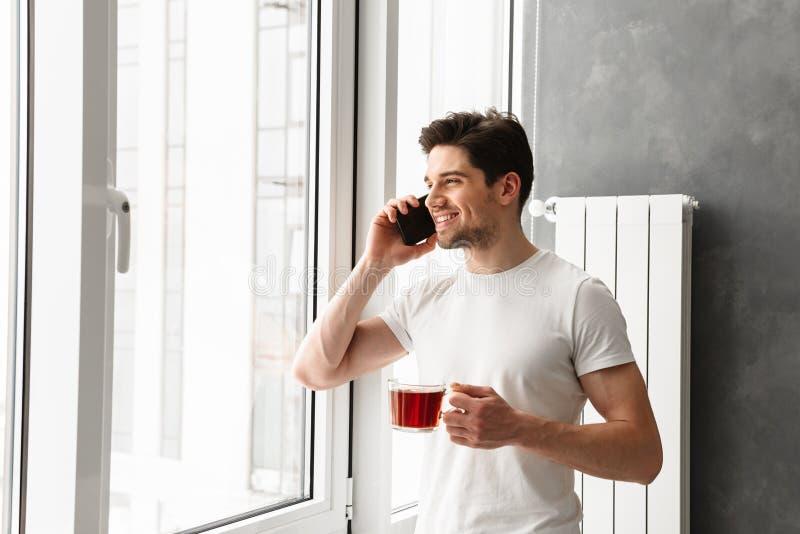 Homem moreno masculino que fala no telefone celular, e olhando para fora fotos de stock
