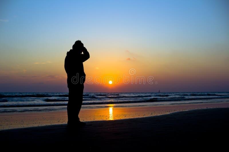 Homem mostrado em silhueta contra um por do sol vívido do oceano foto de stock royalty free