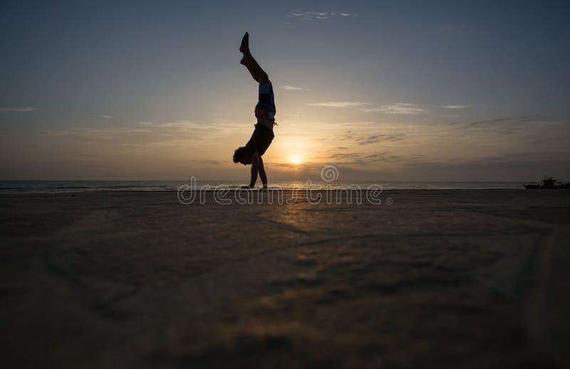Homem mostrado em silhueta que faz o pino no por do sol fotos de stock royalty free