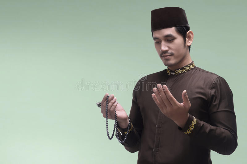 Homem muçulmano asiático considerável que reza ao deus com grânulos de oração imagem de stock