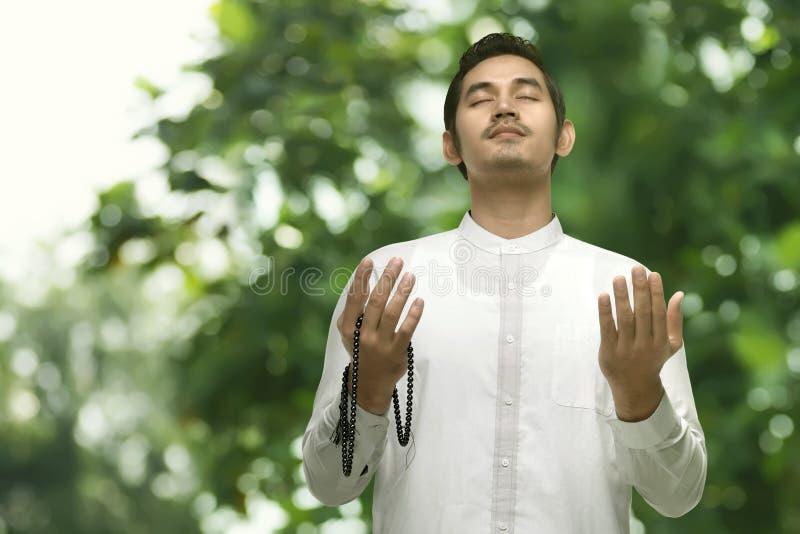 Homem muçulmano asiático novo que reza com grânulos de oração imagens de stock royalty free