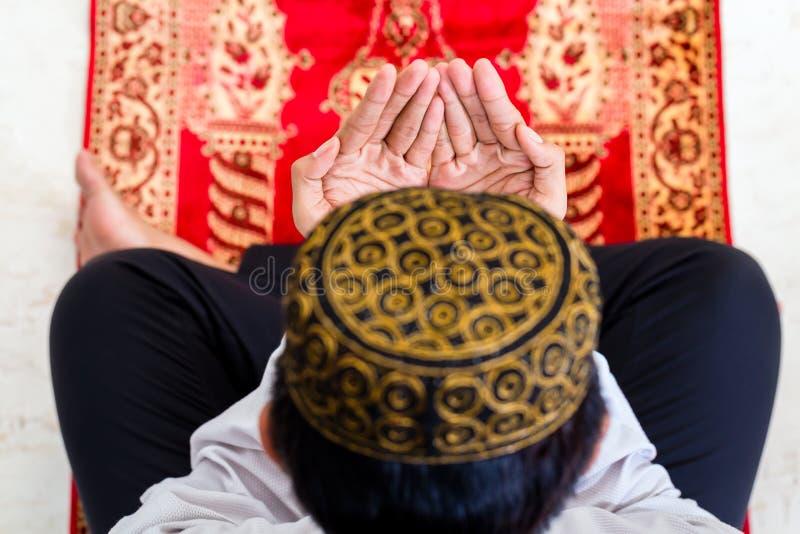 Homem muçulmano asiático que reza no tapete fotografia de stock