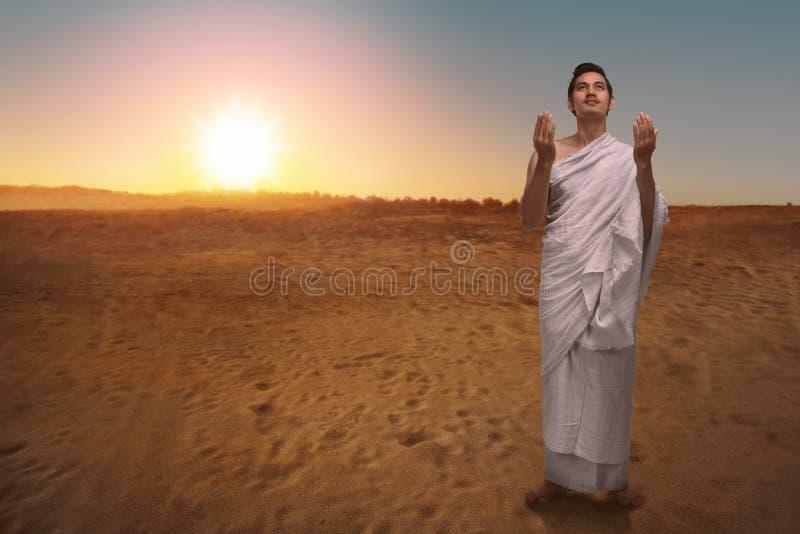 Homem muçulmano asiático religioso no ihram que reza ao deus fotos de stock