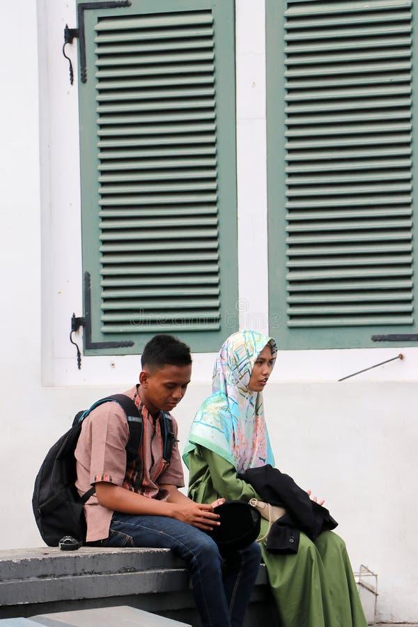 Homem muçulmano e adolescentes fêmeas que sentam-se junto ao lado da janela verde no quadrado de Fatahillah na cidade velha, Jaka fotografia de stock