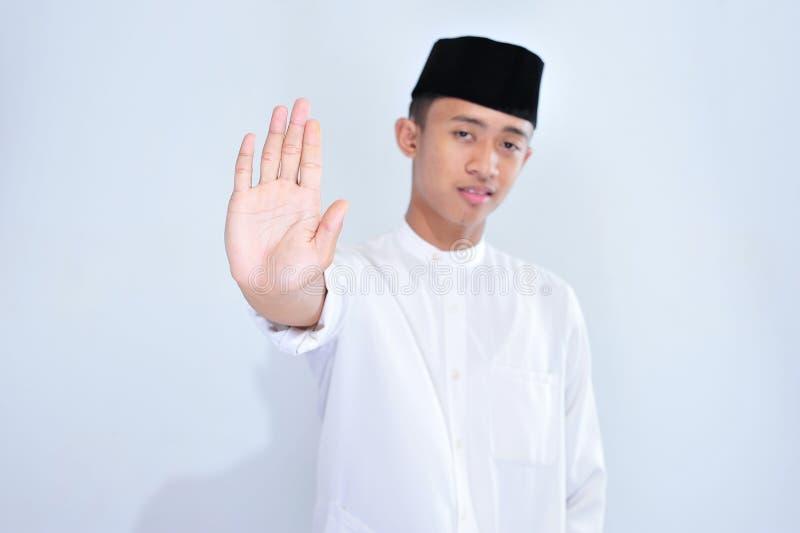 Homem muçulmano novo asiático com a mão aberta que faz o sinal da parada com expressão séria e segura, gesto da defesa fotos de stock