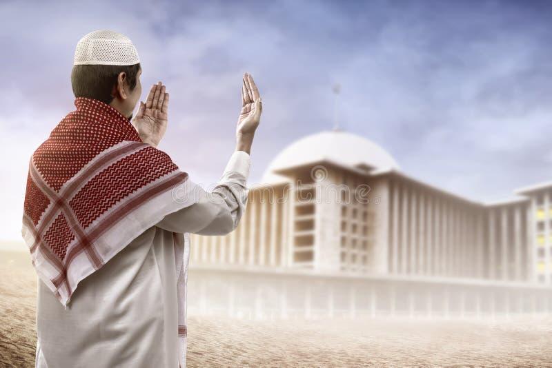 Homem muçulmano novo que reza a vista à mesquita imagens de stock royalty free