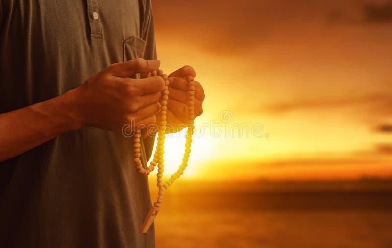 Homem muçulmano religioso que reza com grânulos do rosário imagem de stock