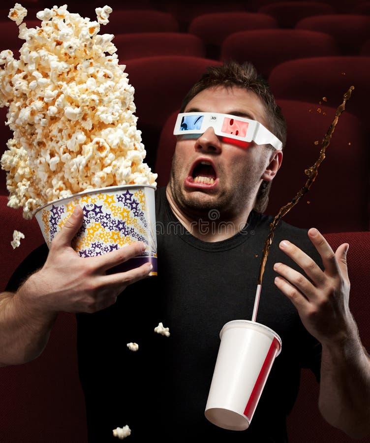 Homem muito scared que presta atenção ao filme 3D fotografia de stock