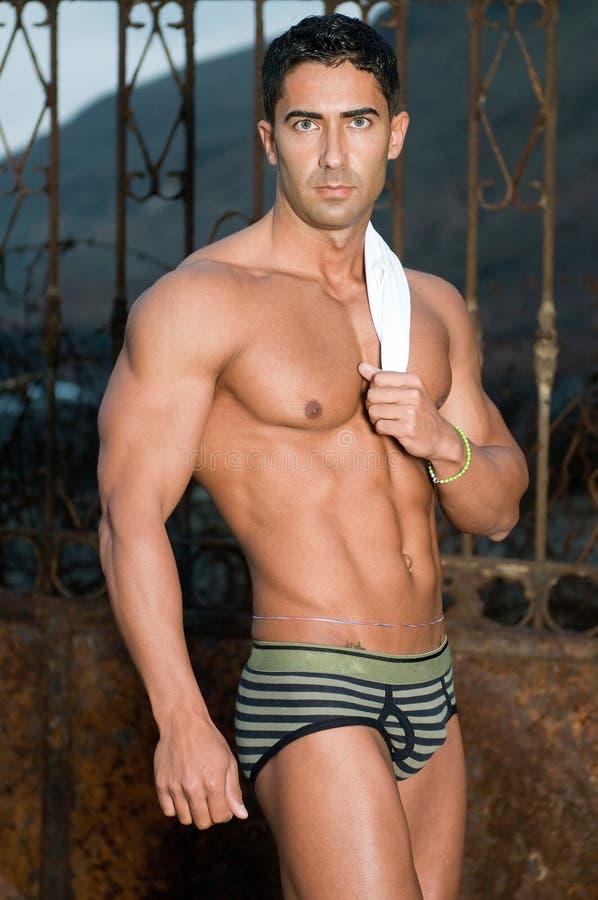 Homem muscled 'sexy' com terno de nadada fotos de stock royalty free