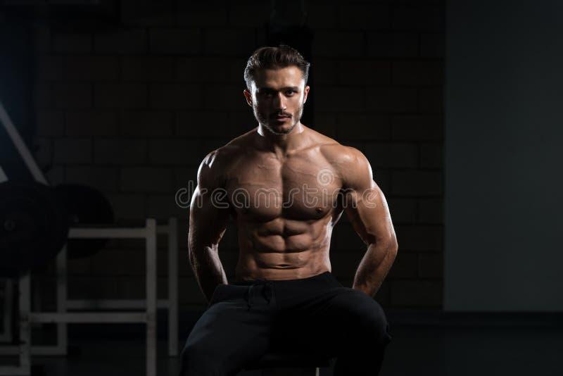 Homem muscular após o exercício que descansa no Gym fotografia de stock royalty free