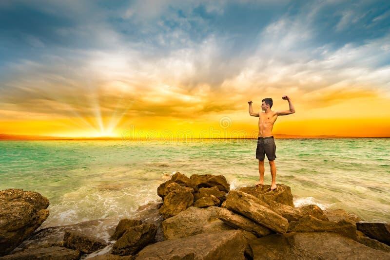 Homem muscular atlético descamisado novo que está na rocha fotografia de stock