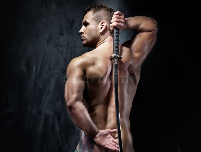 Homem muscular atrativo que levanta com espada. fotografia de stock