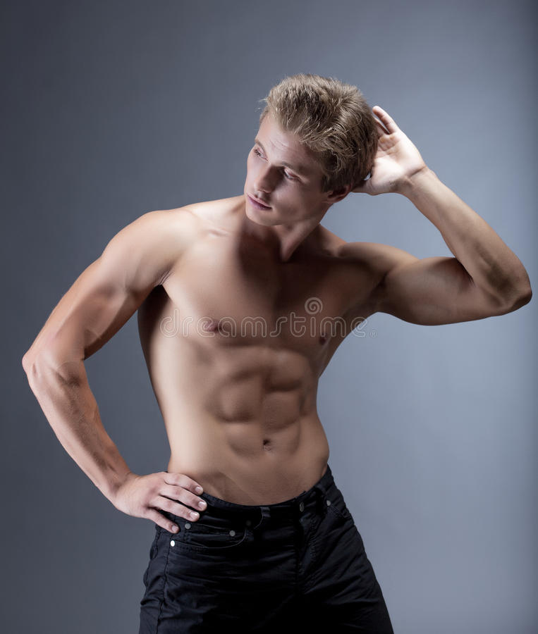 Homem muscular atrativo que levanta com torso despido fotos de stock royalty free