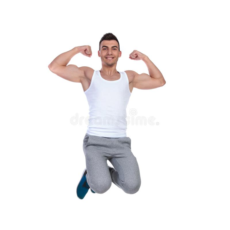 Homem muscular atrativo que salta e que dobra seu bíceps imagem de stock royalty free