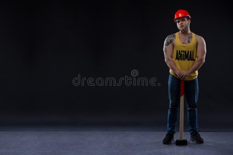 Homem muscular brutal do trabalhador com um martelo imagem de stock royalty free