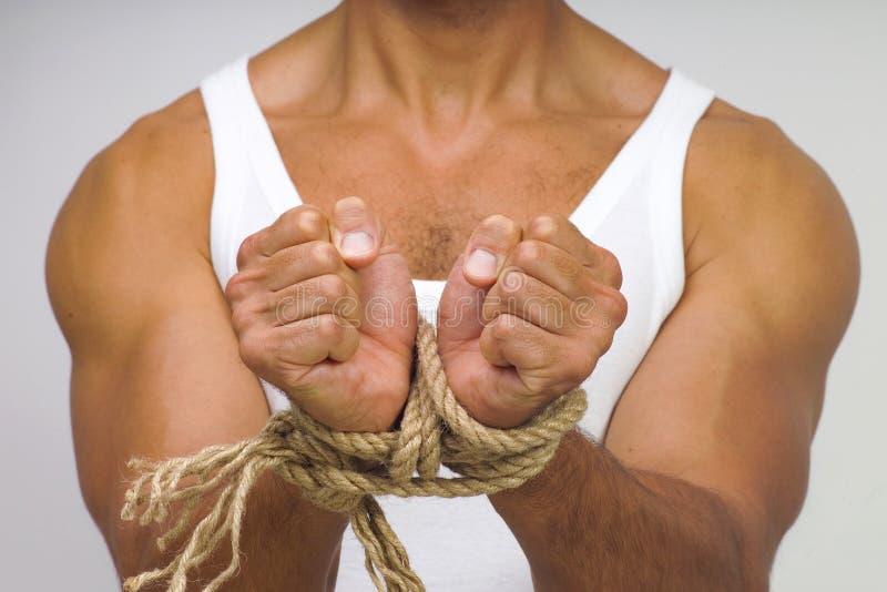Homem muscular com as mãos amarradas pela corda imagem de stock royalty free
