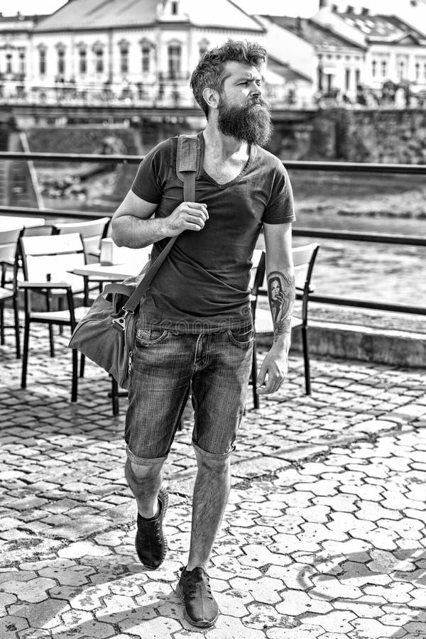 Homem muscular com barba à moda e bigode que leva o saco desportivo grande ao andar na cidade velha Homem novo na sarja de Nimes  imagem de stock royalty free