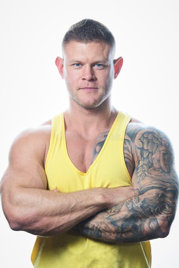 Homem muscular com olhos azuis e tatuagem na camiseta de alças amarela no fundo branco fotos de stock royalty free