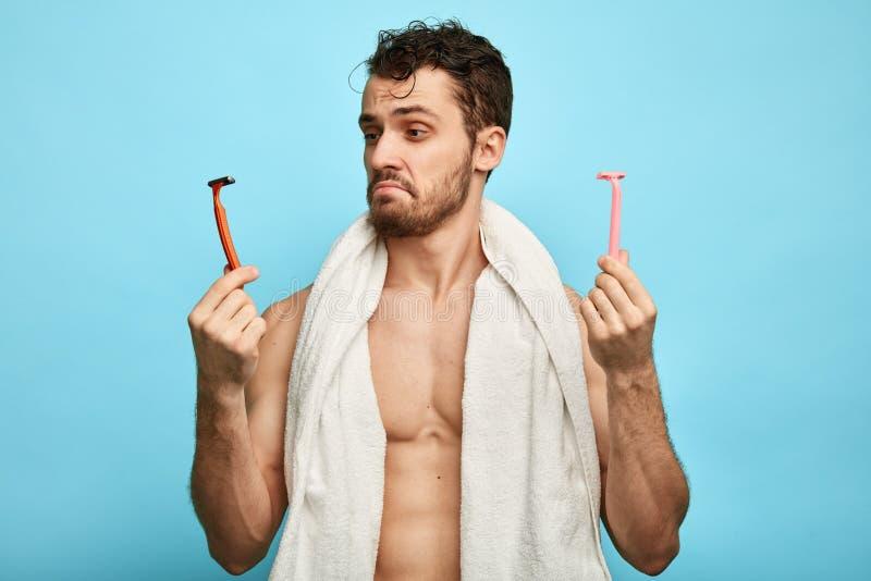 Homem muscular confuso emocional que guarda dois barbeadores imagens de stock