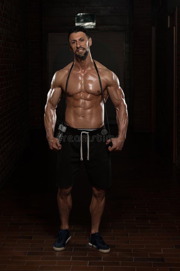 Homem muscular considerável com corda de salto fotos de stock