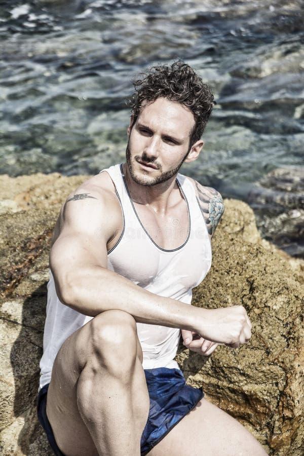 Homem muscular considerável na praia que senta-se em rochas foto de stock
