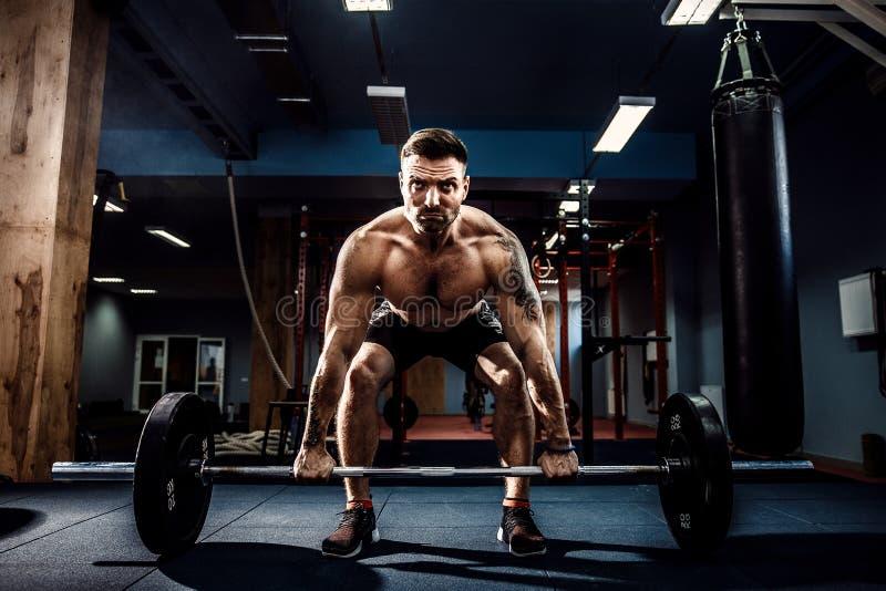 Homem muscular da aptidão que faz o deadlift um barbell no fitness center moderno Treinamento funcional fotos de stock