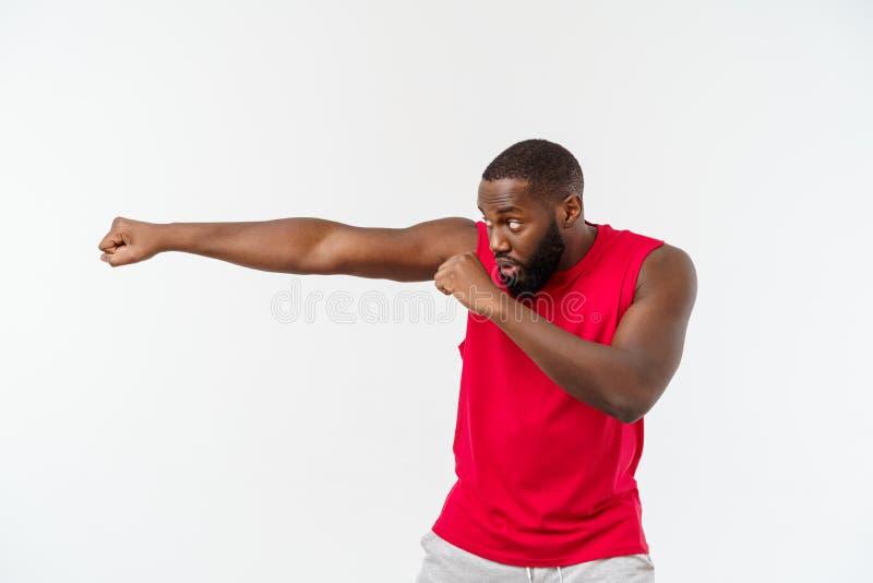 Homem muscular da ascend?ncia africana isolado sobre um fundo branco que mostra um close up de seus punhos e juntas raso fotografia de stock