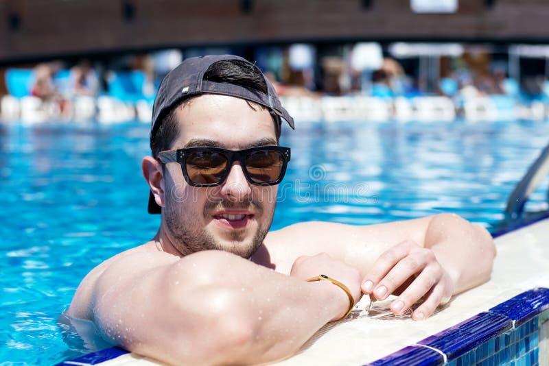Homem muscular de sorriso dos jovens que relaxa na piscina imagens de stock royalty free